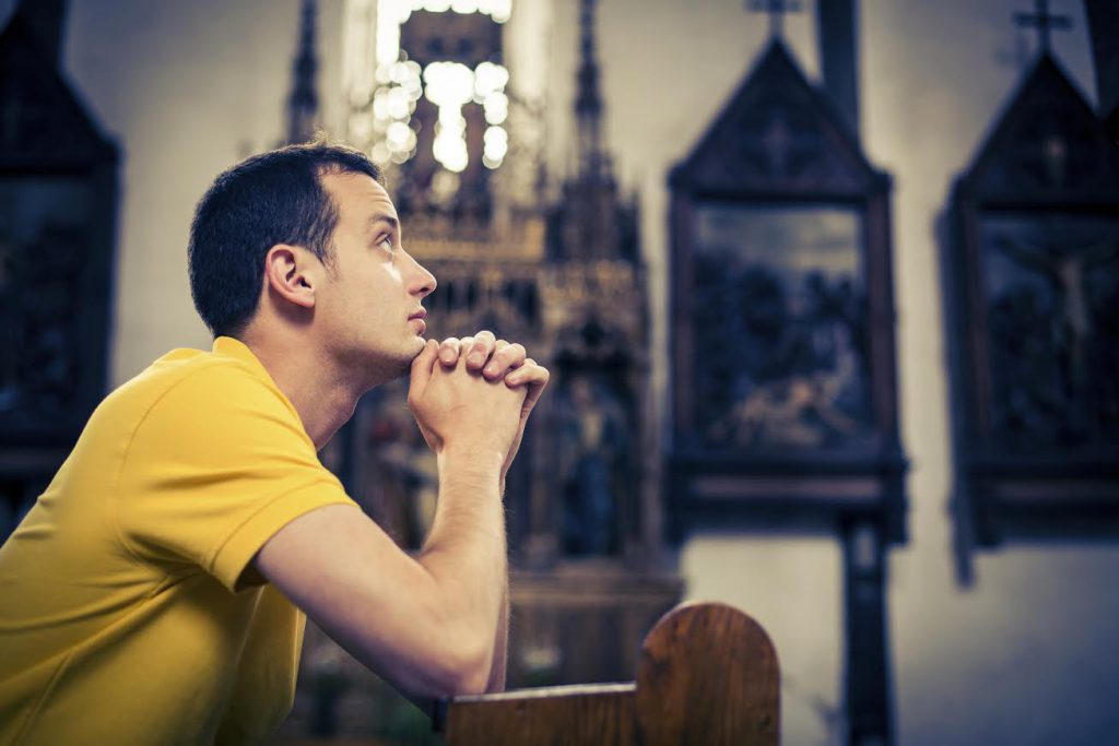 Young man praying in a church